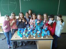 Fünftklässlerinnen präsentieren stolz ihre selbstgebastelten Globen